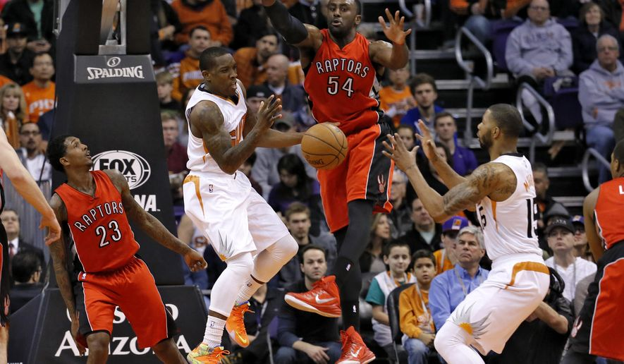 Phoenix Suns' Eric Bledsoe, center, dishes off to Marcus Morris (15) as Toronto Raptors' Patrick Patterson (54) and Lou Williams (23) defend during the first half of an NBA basketball game, Sunday, Jan. 4, 2015, in Phoenix. (AP Photo/Matt York)