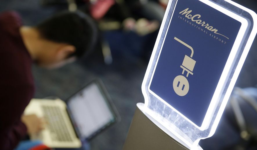 In this Dec. 29, 2014, photo, a man uses a charging station at McCarran International Airport in Las Vegas. By the end of the annual International CES show a couple thousand outlets and USB ports will be available for those looking for a power charge in Terminal 1 before heading home. (AP Photo/John Locher)