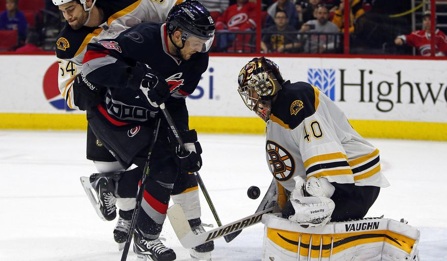 Carolina Hurricanes' Jay McClement (18) gets tied up by Boston Bruins' Adam McQuaid (54) battling for the puck in front of Bruins' goalie Tuukka Rask (40) of Finland, during the second period of an NHL hockey game in Raleigh, N.C., Sunday, Jan. 4, 2015. (AP Photo/Karl B DeBlaker)