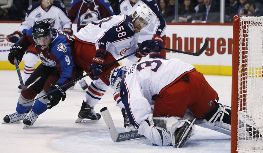 Colorado Avalanche center Matt Duchene, left, attacks the crease as Columbus Blue Jackets defenseman David Savard, center, protects goalie Curtis McElhinney, right, after he stopped a shot and covered the puck in the second period of an NHL hockey game Sunday, Jan. 4, 2015, in Denver. (AP Photo/David Zalubowski)