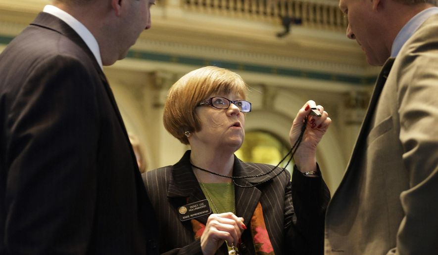 FILE - In this Feb. 15, 2013 file photo, Rep. Dickey Lee Hullingworst, center, D-Boulder, shows House Minority Leader Mark Waller, left, R-Colorado Springs and Rep. Brian DelGrosso, R-Loveland, her whistle as the debate over gun control bills goes on at the Capitol in Denver. In the coming months, Colorado lawmakers will address budgetary surpluses that require refunds to taxpayers, government control over energy development, and a possible overhaul of the medical marijuana industry, issues made more challenging with split-party rule of the state Legislature. (AP Photo/Ed Andrieski, File)