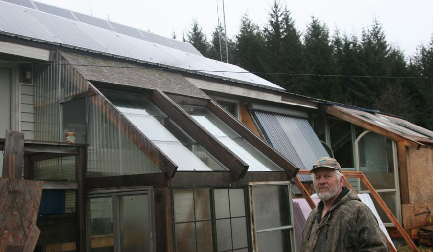 Elk Hunter stands Friday, Dec. 26, 2014, in front of his home in Kake, Alaska, where he installed 16 solar panels on his roof almost two years ago. (AP Photo/The Juneau Empire, Stephanie Shor)