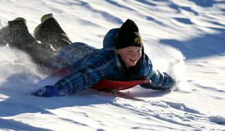In this  Dec. 11, 2013, file photo Zoe Reisen,10, of Dubuque, Iowa, sleds down a hill at Allison-Henderson Park on in Dubuque, Iowa. Faced with the potential bills from people who are injured sledding, Dubuque is one of the cities across the country the is opting to close hills rather than face the risk of large liability claims. (AP Photo/The Telegraph Herald, Jessica Reilly, File)