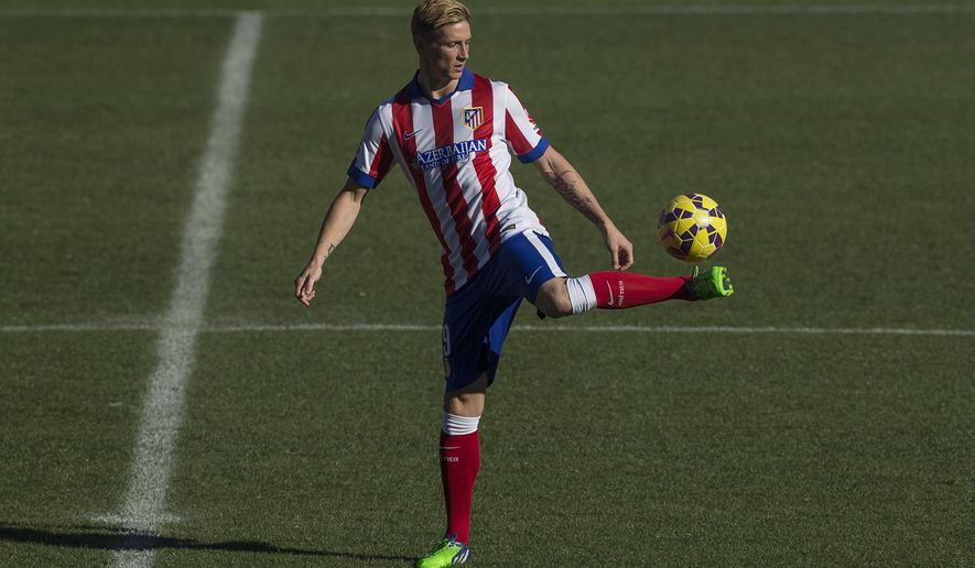 Spanish forward Fernando Torres plays with a ball during his Atletico Madrid's official presentation at the Vicente Calderon stadium in Madrid, Spain, Sunday, Jan. 4, 2015. (AP Photo/Andres Kudacki)