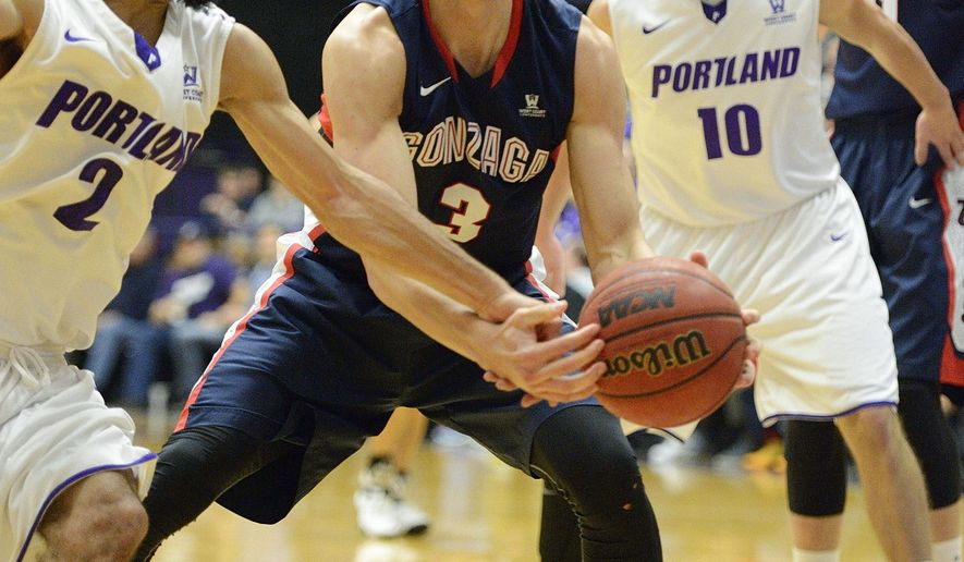 Gonzaga forward Kyle Dranginis (3) battles for a loose ball against Portland guard Alec Wintering (2) during the first half of an NCAA college basketball game in Portland, Ore., Saturday, Jan. 3, 2015. (AP Photo/Troy Wayrynen)