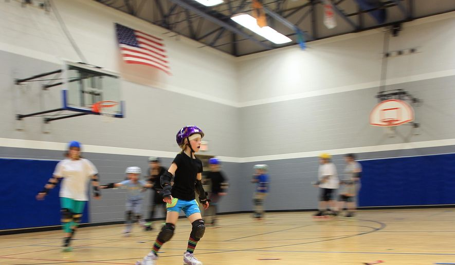 "FOR RELEASE SUNDAY, JANUARY 4, 2015, AT 12:01 A.M. CST. - In this Dec. 15, 2014 photo Michelle ""Wolf Fang"" Babcock practices with the I.C. Bruisers junior roller derby team at Grant Wood Elementary School in Iowa City, Iowa. The I.C. Bruisers, the area's only junior roller derby team, is free for kids 7 to 17 to join and the league has skates and gear available for loan. (AP Photo/Iowa City Press-Citizen, David Scrivner) NO SALES"