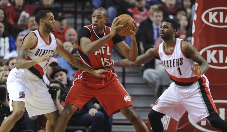 Atlanta Hawks' Al Horford (15) works against Portland Trail Blazers' Allen Crabbe (23) and Dorell Wright (1) during the first half of an NBA  basketball game in Portland, Ore., Saturday, Jan. 3, 2015. (AP Photo/Greg Wahl-Stephens)