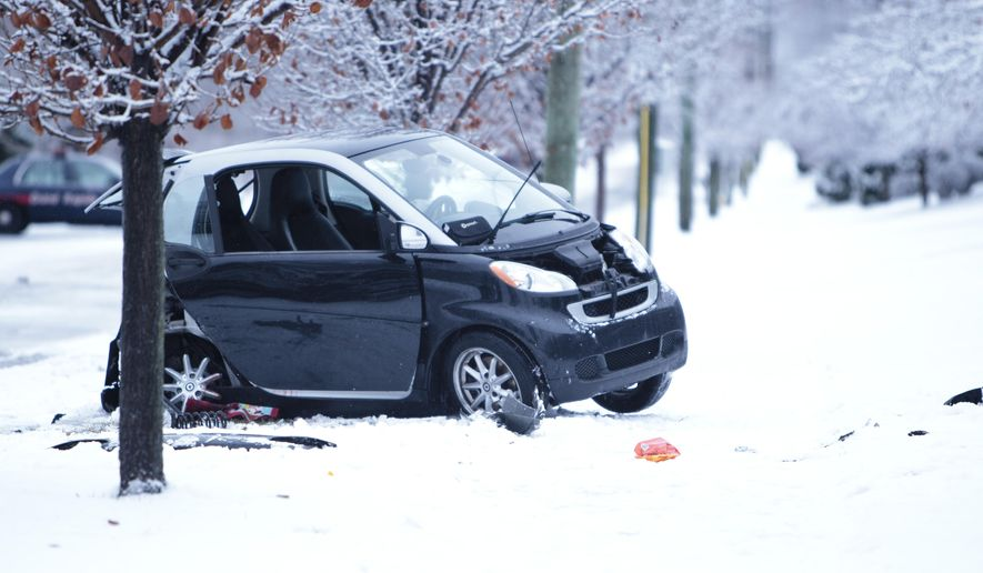 The scene an accident is left near an intersection in Grand Rapids, Mich., Sunday, Jan. 4, 2015. The National Weather Service said an Arctic front was bringing cold and windy conditions across Michigan's Lower Peninsula, while up to a foot of snow was expected in the Upper Peninsula. (AP Photo/The Grand Rapids Press, Joel Bissell)