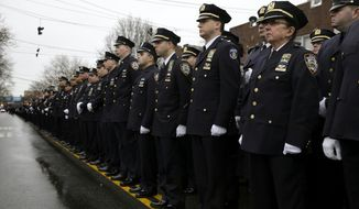 Police officers line the streets before the funeral of Officer Wenjian Liu in the Brooklyn borough of New York, Sunday, Jan. 4, 2015. Liu and his partner, officer Rafael Ramos, were killed Dec. 20 as they sat in their patrol car on a Brooklyn street. The shooter, Ismaaiyl Brinsley, later killed himself.   (AP Photo/Seth Wenig)