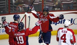 Washington Capitals left wing Andre Burakovsky (65), from Austria, left wing Alex Ovechkin (8), from Russia, center Nicklas Backstrom (19), from Sweden, celebrate a goal by Burakovsky with Florida Panthers defenseman Dylan Olsen (4) nearby, in the third period of an NHL hockey game, Sunday, Jan. 4, 2015, in Washington. The Capitals won 4-3. (AP Photo/Alex Brandon)