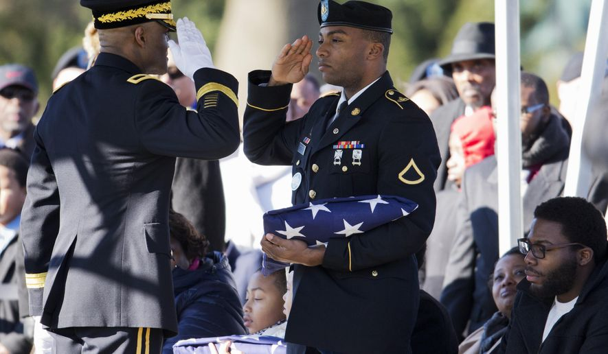 Devin Turner, the son of U.S. Army Sgt. Maj. Wardell B. Turner, right, salutes as he is presented with an American flag by Army Brig. Carl Alex, left, during a burial services at Arlington National Cemetery in Arlington, Va., Monday, Jan. 5, 2015. According to the Defense Department, Sgt. Maj. Turner, 48, of Nanticoke, Md., died Nov. 24, 2014, in Kabul, Afghanistan, of wounds suffered when the enemy attacked their vehicle with a vehicle borne improvised explosive device. He was assigned to Headquarters, United States Army Garrison, Fort Drum, New York.  (AP Photo/Manuel Balce Ceneta)