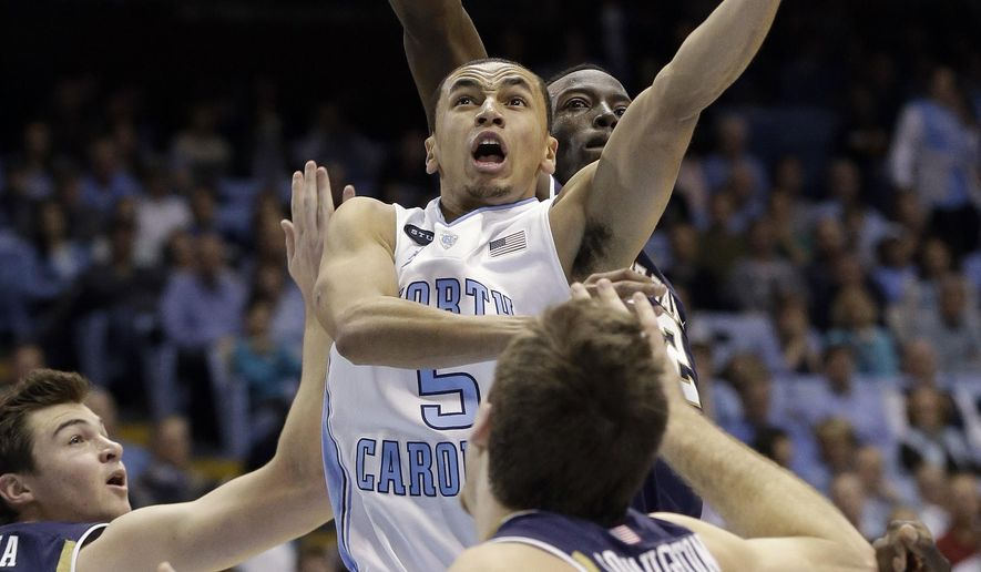 North Carolina's Marcus Paige (5) drives to the basket as Notre Dame's Steve Vasturia, left, and Pat Connaughton, right, defend during the first half of an NCAA college basketball game in Chapel Hill, N.C., Monday, Jan. 5, 2015. (AP Photo/Gerry Broome)
