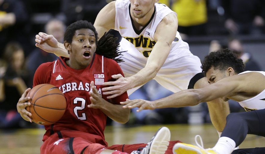 Nebraska forward David Rivers, left, picks up a loose ball in front of Iowa's Jarrod Uthoff, center, and Dominque Uhl, right, during the first half of an NCAA college basketball game, Monday, Jan. 5, 2015, in Iowa City, Iowa.(AP Photo/Charlie Neibergall)