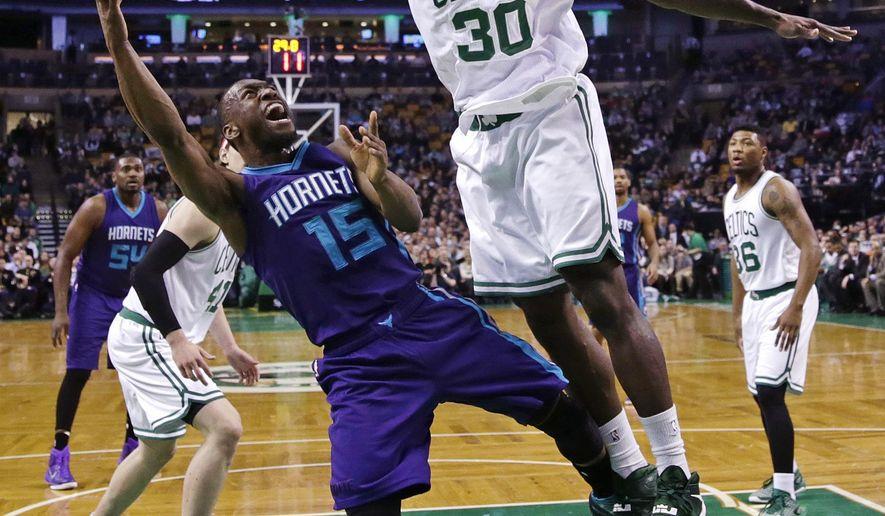 Boston Celtics forward Brandon Bass (30) leaps high to block a shot by Charlotte Hornets guard Kemba Walker (15) during the first quarter of an NBA basketball game in Boston, Monday, Jan. 5, 2015. (AP Photo/Charles Krupa)