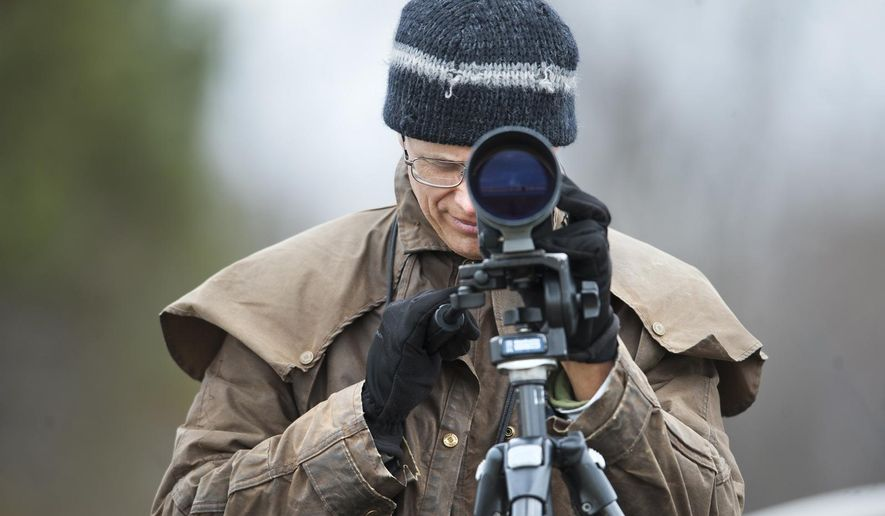 In this Sunday, Jan. 4, 2015 photo, Dave Mozurkewich of Lanham uses a high-powered scope to identify the numbers and species of birds flying around Sandy Point State Park, in Annapolis, Md., part of a gathering of bird watchers collecting data during the annual Christmas Bird Count, which ends Monday. (AP Photo/Capital Gazette, Joshua McKerrow)