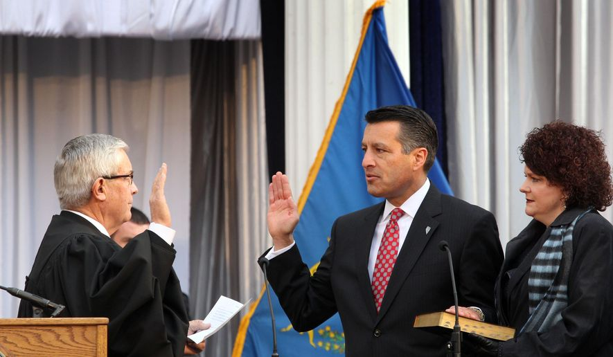 Nevada Gov. Brian Sandoval, center, holds his hand on a bible held by his wife first lady Kathleen Sandoval as he takes the oath of office during his inauguration ceremony on the front steps of the capital in Carson City, Nev., Monday, Jan. 5, 2015. (AP Photo/Lance Iversen)