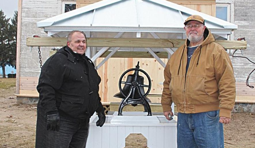 In a Dec. 30, 2014 photo, Burr Oak Community Schools Superintendent Terry Conklin, left, and Sheldon Fieberkorn stand next to the returned bell in Sturgis, Mich. The historic Worden School bell had been missing for the last 40 years, stolen in 1974, but on Dec. 30 was placed back atop the school building. Fieberkorn was instrumental in finding the original bell and had been looking for it for the last two years. Fieberkorn said the family in possession of the bell agreed to return it on the condition that they would remain anonymous. (AP Photo/Sturgis Journal, Michelle Patrick)