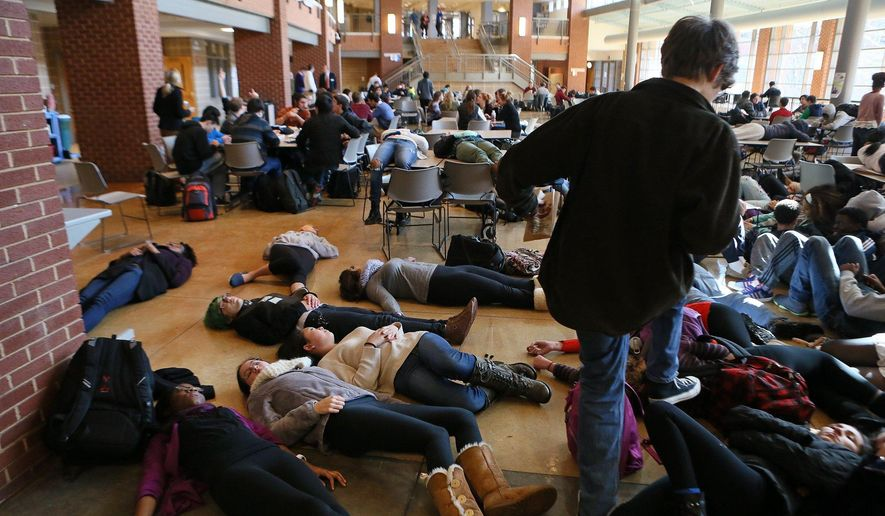 FILE - In this Dec. 1, 2014 file photo, students participating in a die lie on the cafeteria floor at Clayton, Mo., High School following a grand jury's decision not to indict a white police officer who killed 18-year-old black Michael Brown. The American Civil Liberties Union filed the lawsuit Monday, Jan. 5, 2015 on behalf of a jury member asking a Missouri court to remove a lifetime order that prevents jurors from discussing the case.  (AP Photo/St. Louis Post-Dispatch,  Cristina Fletes-Boutte, File)