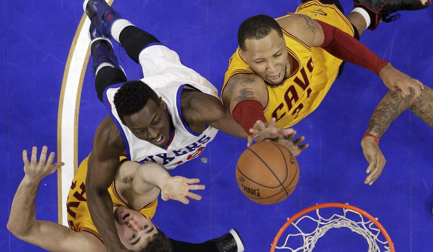 Cleveland Cavaliers' Shawn Marion, right, and Joe Harris, left, go up for a rebound against Philadelphia 76ers' Jerami Grant during the first half of an NBA basketball game, Monday, Jan. 5, 2015, in Philadelphia. (AP Photo/Matt Slocum)