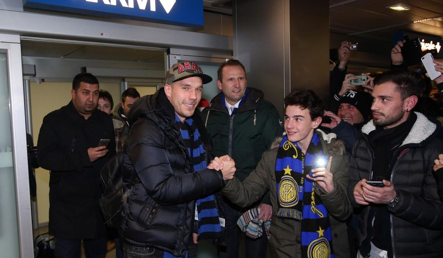 German forward Lukas Podolski, second from left, shakes hands with supporters as he arrives at the Linate airport, Milan, Italy, Friday, Jan. 2, 2015. Podolski is joining the Serie A club Inter Milan. (AP Photo/Ansa/Matteo Bazzi)