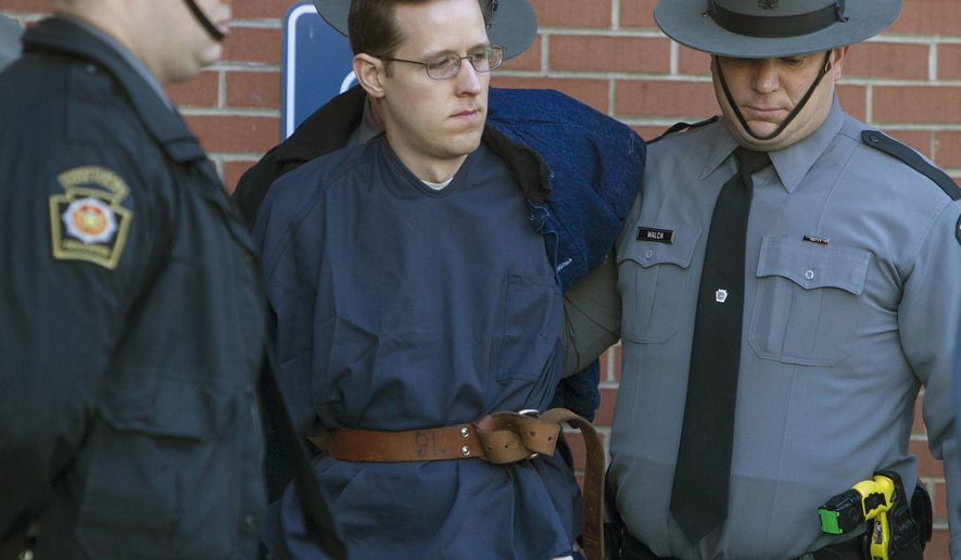 Eric Frein, center, is escorted out of the Pike County Courthouse after his preliminary hearing in Milford, Pa., Monday, Jan. 5, 2015. Frein is charged with fatally shooting a Pennsylvania state trooper and wounded another during an ambush at their barracks in September. A judge on Monday ordered Frein to stand trial on the charges. Prosecutors are seeking the death penalty. Frein led authorities on a 48-day manhunt through the Pocono woods before marshals captured him at an abandoned airplane hangar. (AP Photo/PennLive.com, Mark Pynes )