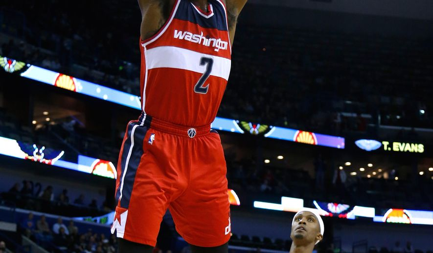 Washington Wizards guard John Wall (2) dunks over New Orleans Pelicans forward Dante Cunningham (44) during the first half of an NBA basketball game, Monday, Jan. 5, 2015, in New Orleans. (AP Photo/Jonathan Bachman)