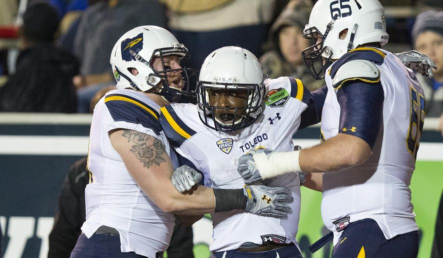 Toledo running back Kareem Hunt (3) celebrates with tight end Zac Rosenbauer (41) offensive lineman Chase Nelson (65) after Hunt scored a touchdown during the first half of the GoDaddy Bowl NCAA college football game against Arkansas State, Sunday, Jan. 4, 2015, in Mobile, Ala. (AP Photo/Brynn Anderson)