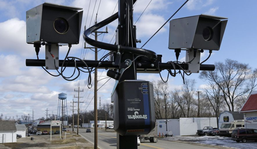 FILE - This Tuesday, Feb. 25, 2014, file photo, shows speed cameras aimed at U.S. Route 127 in New Miami, Ohio. One of the early users of traffic camera enforcement in Ohio announced Monday, Jan. 5, 2015, it will stop using fixed-position cameras because of a new state law. Dayton has used camera enforcement for more than a decade, but city police spokeswoman Cara Zinski-Neace said budgetary considerations led to the decision to curtail their use when the Ohio law takes effect in March.  The law passed last month regulates statewide use of the devices and requires that a police officer be present for camera-issued citations. (AP Photo/Al Behrman, File)