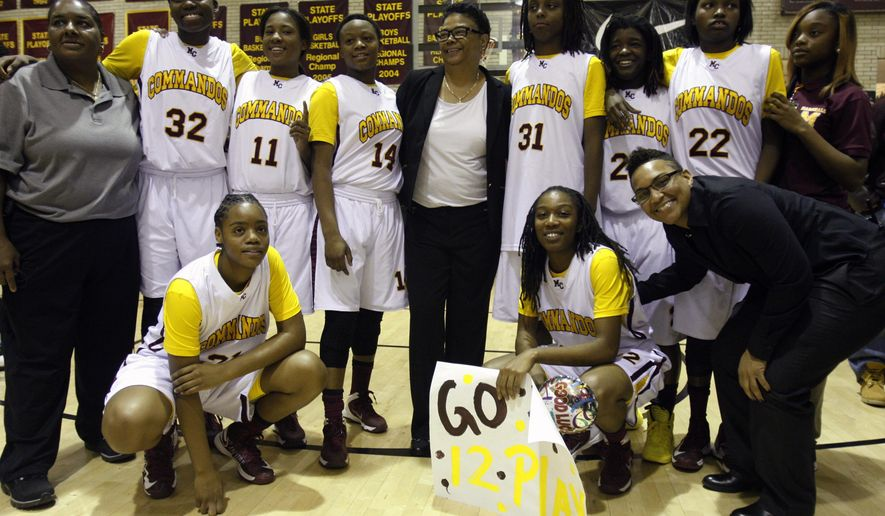 Dorothy Gaters, center, coach of the girls' basketball team at John Marshall Preparatory High School, poses for photos with her team and assistant coaches after her 1,000th career win on Tuesday, Nov. 18, 2014, in Chicago. Gaters has won more games than any high school basketball coach in Illinois, boys or girls. The back row includes Gwen Howard, left, a former player who is now an assistant coach; Tineesha Coleman, second from left; Temya Russell, fourth from left; and Juliunn Redmond, second from right. (AP Photo/Martha Irvine)