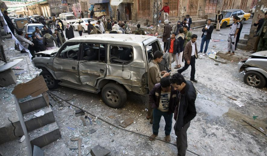FILE - In this Tuesday, Dec. 23, 2014 file photo, Shiite Houthi men stand near a car damaged by a bomb explosion outside their house in Sanaa Yemen. Houthi rebels in September seized control of the capital, Sanaa, and are allied with loyalists of former president, Ali Abdullah Saleh. The Houthis' power grab has been  met with suicide bombings and deadly attacks, mainly by Sunni rivals from al-Qaida and allied tribes. (AP Photo/Hani Mohammed)