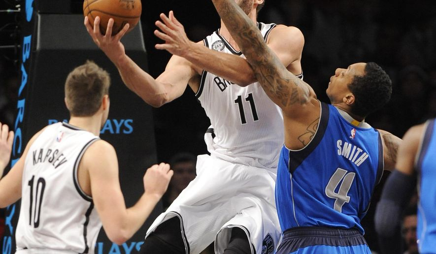 Brooklyn Nets center Brook Lopez (11) goes up for a basket against Dallas Mavericks forward Greg Smith (4) as Nets guard Sergey Karasev (10) watches during the first half of an NBA basketball game Monday, Jan. 5, 2015, in New York. (AP Photo/Kathy Kmonicek)