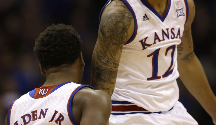 Kansas guards Kelly Oubre Jr. (12) and Wayne Selden Jr. (1) celebrate at a timeout during the first half of an NCAA college basketball game against UNLV in Lawrence, Kan., Sunday, Jan. 4, 2015. Kansas defeated UNLV 76-61. (AP Photo/Orlin Wagner)