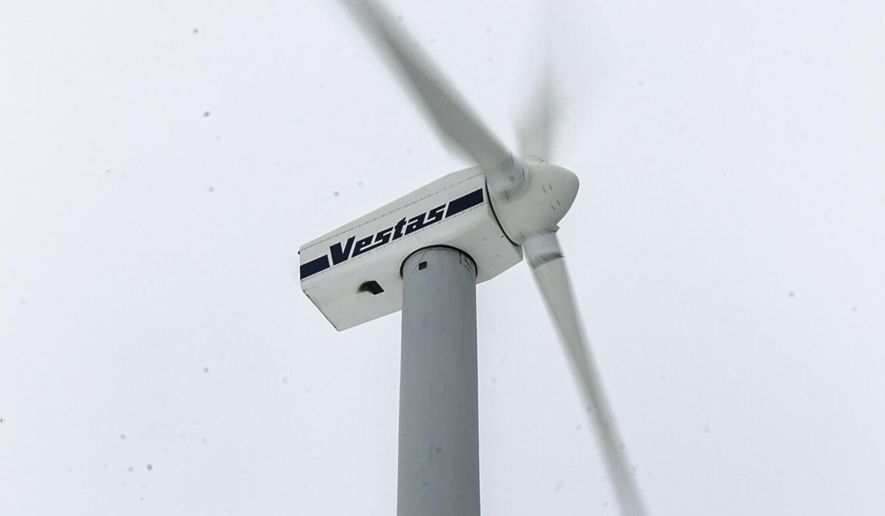 A 160-foot-tall wind turbine spins off M-72 west of Traverse City, Mich. The new owners of Michigan's first utility-grade wind turbine have been told they must obtain a zoning permit before it can begin operating again. (AP Photo/Traverse City Record-Eagle, Pete Rodman)