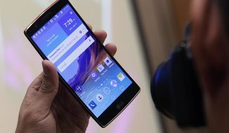 A man photographs the LG G Flex 2 during a media preview before CES International Sunday, Jan. 4, 2015, in Las Vegas. The phone has a curved screen, as the name implies.(AP Photo/John Locher)