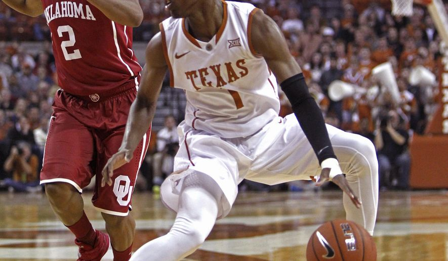 Texas guard Isaiah Taylor (1) looks to drive against Oklahoma guard Dinjiyl Walker (2) during the first half an NCAA college basketball game, Monday, Jan. 5, 2015, in Austin, Texas. (AP Photo/Michael Thomas)