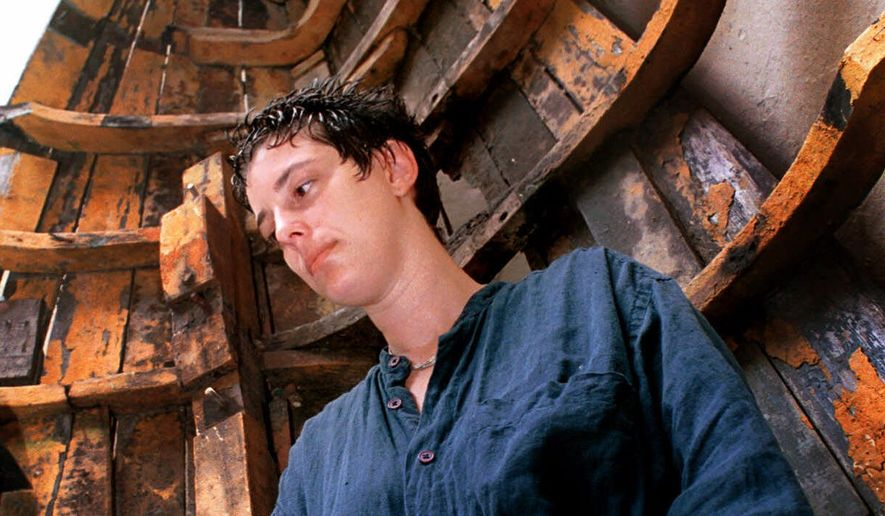 In this Sept. 9, 2000 photo, Cuban artist Tania Bruguera stands in front of one of her art pieces, a representation of a raft, in Havana. ( AP Photo/Cristobal Herrera)