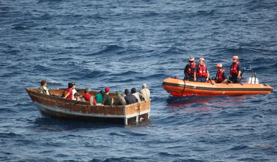 In this Dec. 30, 2014, photo provided by the U.S. Coast Guard, members of the U.S. Coast Guard Cutter Knight Island approach a boat with 12 Cuban migrants southwest of Key West, Fla. The Cuban migrants were repatriated to Cabanas, Cuba. Coast Guard officials said Monday, Jan. 5, 2015, that the number of Cubans attempting to reach Florida illegally by sea has surged since the U.S. and Cuba announced they would restore diplomatic relations. (AP Photo/U.S. Coast Guard)