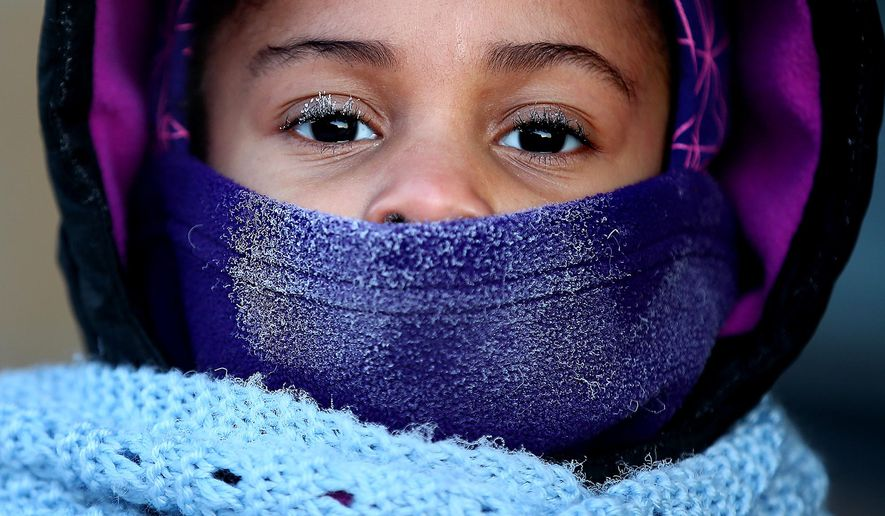 Despite the ice developing on her face, Treashure Whitney-Taylor walks to Trinity First Elementary School with her father, Monday, Jan.5, 2015, in Minneapolis. (AP Photo/The Star Tribune, Elizabeth Flores)