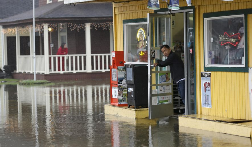 A shopkeeper eyes floodwaters outside his store, Monday, Jan. 5, 2015 in Hoquiam, Wash. A weekend storm blasted parts of western Washington with torrential rain that caused landslides and flooding, including in Hoquiam where water washed out the foundations of three homes, threatened others and forced the evacuation of about 60 nursing home residents, authorities said. (AP Photo/Ted S. Warren)