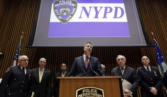"New York Mayor Bill de Blasio, center, accompanied by New York City Police Commissioner William Bratton, second from right, and other ranking NYPD officers, addresses a news conference at New York City Police headquarters, Monday, Jan. 5, 2015. De Blasio says it was ""disrespectful"" that some NYPD officers turned their backs to him during a pair of funerals for slain police officers. (AP Photo/Richard Drew)"