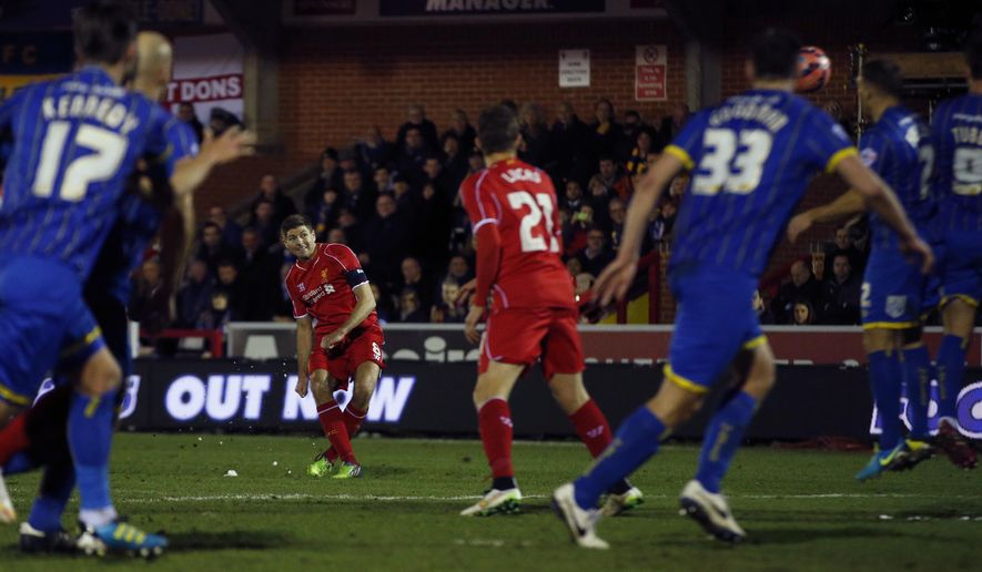 Liverpool's Steven Gerrard, centre, scores his sides second goal from a direct free kick during their English FA Cup third round soccer match between AFC Wimbledon and Liverpool in Kingston, London, Monday, Jan.  5, 2015 . (AP Photo/Alastair Grant)