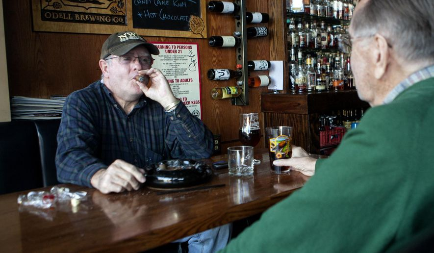 In this Sunday, Jan. 4, 2015 photo, John Burkman, left, smokes a cigar while enjoying a drink at Jake's Cigars and Spirits in Lincoln, Neb. Monday will be the final day of smoking cigars in the bar. (AP Photo/The Journal-Star, Matt Masin) LOCAL TELEVISION OUT; KOLN-TV OUT; KGIN-TV OUT; KLKN-TV OUT