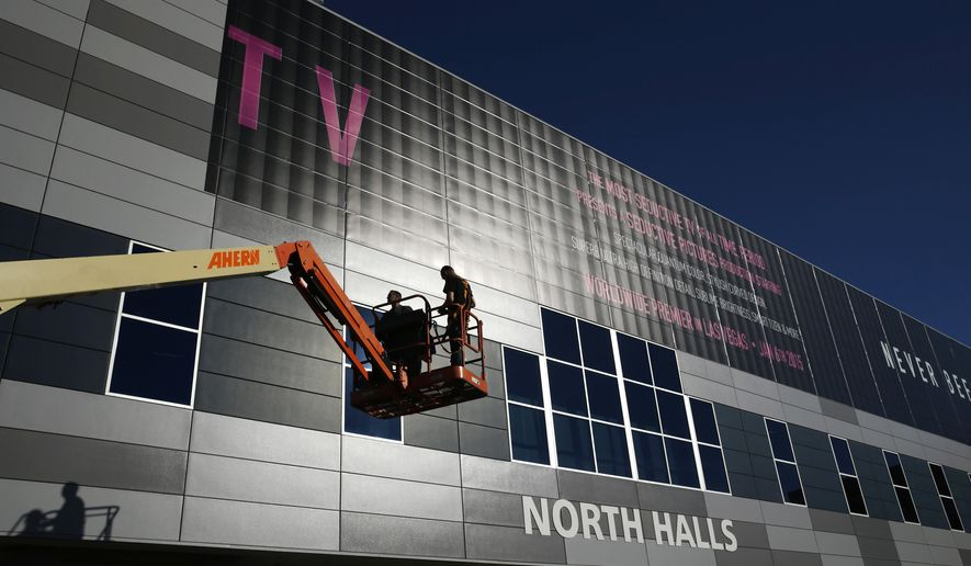 Workers install a sign in preparation for International CES at the Las Vegas Convention Center on Sunday, Jan. 4, 2015, in Las Vegas. The International CES convention starts Tuesday. (AP Photo/John Locher)