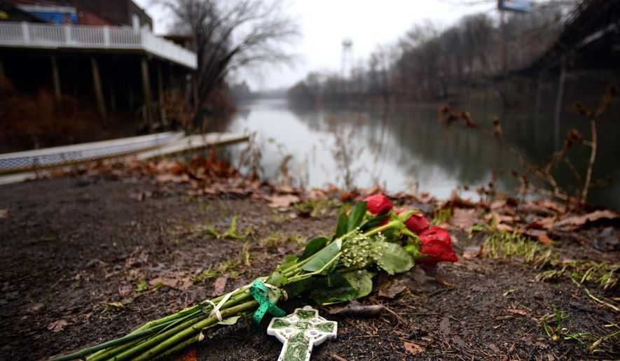 A Celtic cross and roses with a green ribbon are left on the scene in the Manayunk neighborhood of Philadelphia,  Sunday, Jan. 4, 2015, the day after the body of Shane Montgomery was found in the Schuylkill River. (AP Photo/The Philadelphia Inquirer, Tom Gralish)