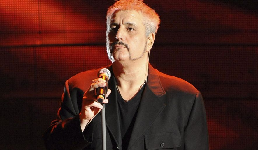 """FILE - In this Thursday, Feb. 19, 2008 file photo, Pino Daniele Performs during the """"Festival di Sanremo"""" Italian song contest, in San Remo, Italy. inger, songwriter and guitarist Pino Daniele, whose fusion of blues and jazz was greatly inspired by the beauty and ugliness of his native Naples, has died. He was 59.  Carlo Saitto, an official at Sant'Eugenio hospital in Rome, told Italian state TV that Daniele died Sunday, Jan. 4, 2015, night soon after arriving with grave cardiac and respiratory problems. Daniele, with a history of heart trouble, had given a New Year's concert in Italy last week. The musician was so identified with Naples that the city's mayor ordered flags flown at half-mast. Daniele's style was constantly evolving, as he experimented with blues and jazz. His voice, sexy, bordering on hoarse, was expressive, like his fellow Neapolitans. Some of his songs mixed Neapolitan dialect with Italian. He played with jazz stars like Wayne Shorter. (AP Photo/Antonio Calanni, File)"""