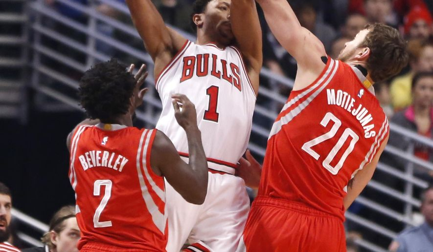 Houston Rockets' Donatas Motiejunas (20) and Patrick Beverley (2) pressure Chicago Bulls guard Derrick Rose (1) during the first half of an NBA basketball game Monday, Jan. 5, 2015, in Chicago. (AP Photo/Charles Rex Arbogast)