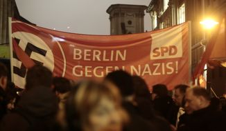 Demonstrators stand in front of a banner of German Social Democratic party (SPD) with a crossed-out swastika and the slogan 'Berlin against Nazis' to protest against a planned rally of  the so-called 'Berlin Patriots against the Islamization of the West' (BAERGIDA) in Berlin, Monday, Jan. 5, 2015. (AP Photo/Markus Schreiber)