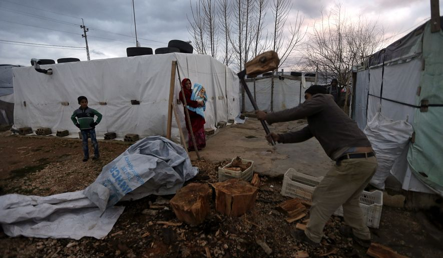 A Syrian refugee man, cuts wood as he prepares for the possibility of a snow storm at a Syrian refugee camp, in Deir Zannoun village, Bekaa valley, Lebanon, Monday, Jan. 5, 2015. A snow storm is expected to hit Lebanon Monday affecting Syrian refugees, many of whom live in tents without proper heating. The government estimates there are about 1.5 million Syrians in Lebanon, about one-quarter of the total population. (AP Photo/Hussein Malla)