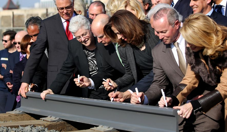 Gov. Jerry Brown, fifth from right,  and his wife Anne Gust, fourth from right, sign a portion of the rail at the California High Speed Rail Authority ground breaking event as Gina McCarthy, administrator of the U.S. Environmental Protection Agency, standing next to Brown at left, watches, Tuesday, Jan. 6, 2015 in Fresno, Calif. Gina McCarthy. California's high-speed rail project has become the first in the nation to break ground.  Tuesday's groundbreaking was attended by several hundred people who gathered near old rail lines in an industrial section of downtown Fresno. (AP Photo/Gary Kazanjian)