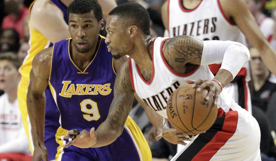 Portland Trail Blazers guard Damian Lillard, right, drives on Los Angeles Lakers guard Ronnie Price during the first half of an NBA basketball game in Portland, Ore., Monday, Jan. 5, 2015. (AP Photo/Don Ryan)